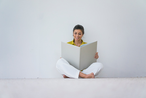 Smiling woman sitting on the floor reading oversized book - gettyimageskorea