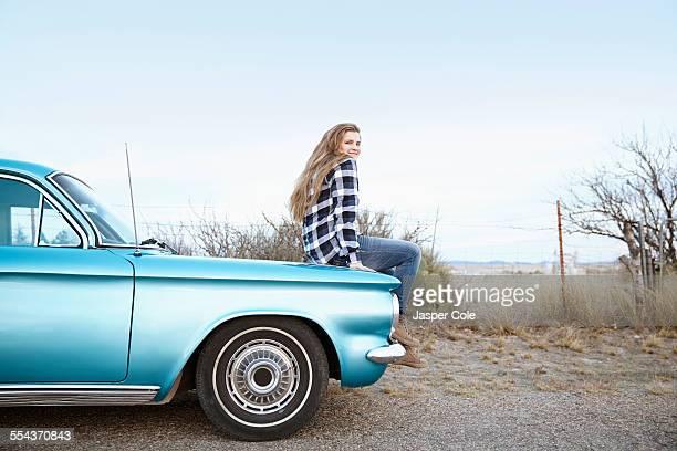 Smiling woman sitting on vintage car