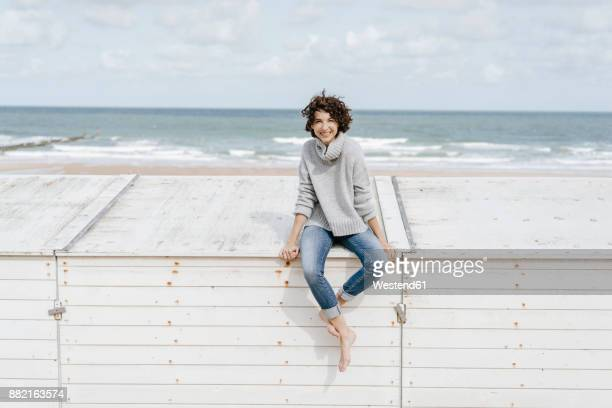 Smiling woman sitting on wooden box on the beach