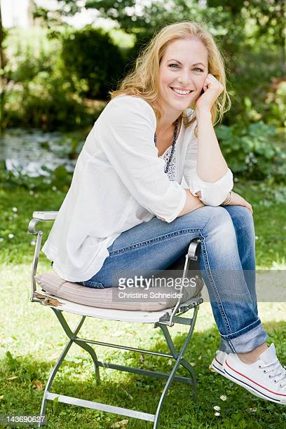 smiling woman sitting outdoors - une seule femme d'âge moyen photos et images de collection