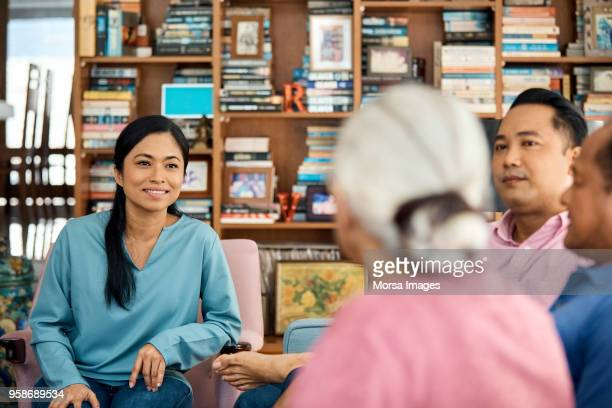 Smiling woman sitting with family at home