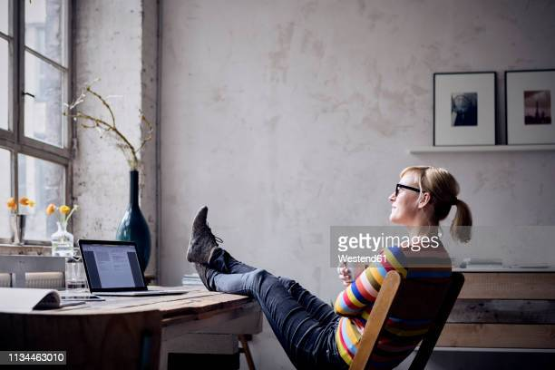 smiling woman sitting with feet up at desk in a loft looking through window - coffee break stock pictures, royalty-free photos & images