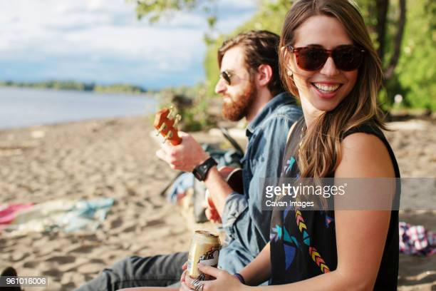 Smiling woman sitting with friend playing ukulele