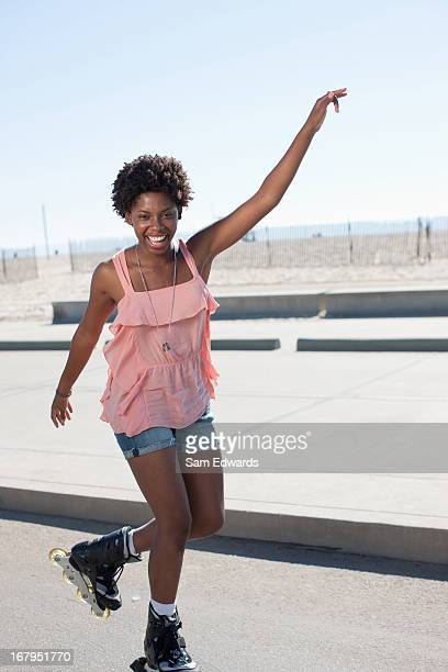 smiling woman skating in park - inline skating stock pictures, royalty-free photos & images