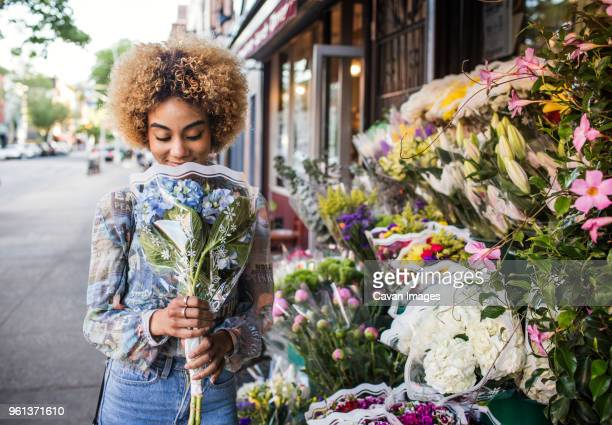Smiling woman smelling hydrangeas outside flower shop