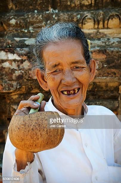 Smiling woman smoking a cheroot in Bagan, Burma