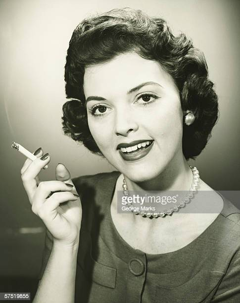 smiling woman smoking cigarette in studio, (b&w), close-up, portrait - femme qui fume photos et images de collection