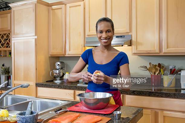 Smiling woman squeezing fresh lemon juice