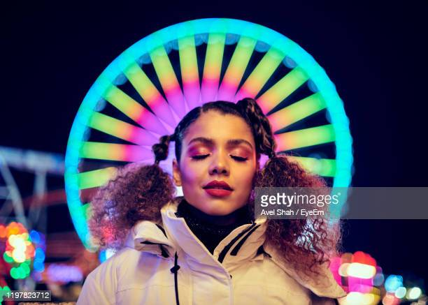 smiling woman standing against illuminated ferris wheel at night - focus on foreground stock pictures, royalty-free photos & images