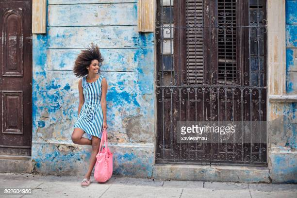 smiling woman standing against weathered building - striped dress stock pictures, royalty-free photos & images