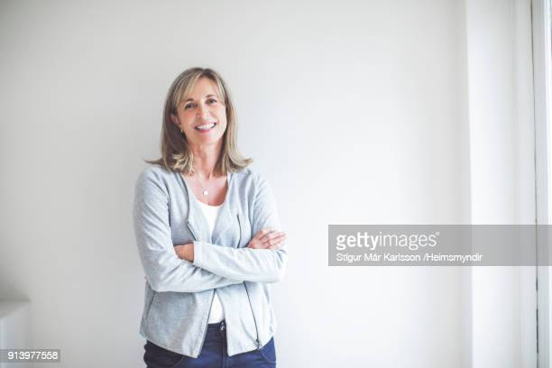 smiling woman standing arms crossed against wall - donna 50 anni foto e immagini stock