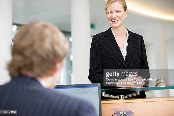 "smiling woman standing at a desk - ""compassionate eye"" fotografías e imágenes de stock"