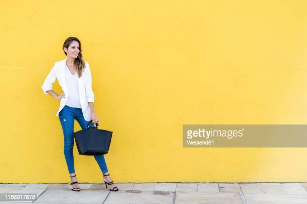 smiling woman standing at a yellow wall holding a handbag - clutch bag stock pictures, royalty-free photos & images