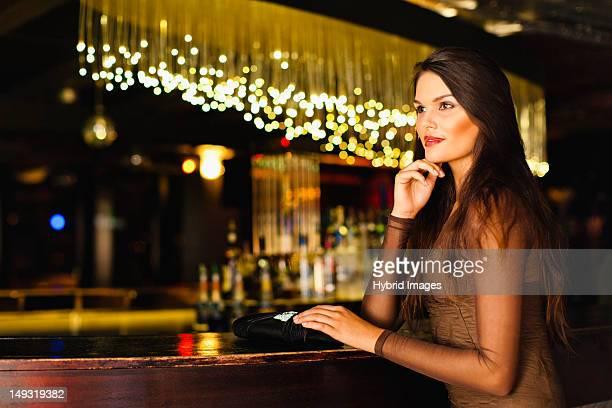 Smiling woman standing at bar