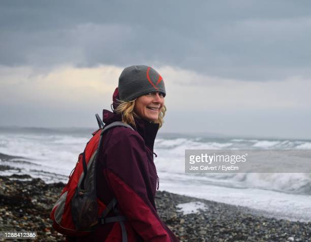 smiling woman standing at beach against sky - warm clothing stock pictures, royalty-free photos & images