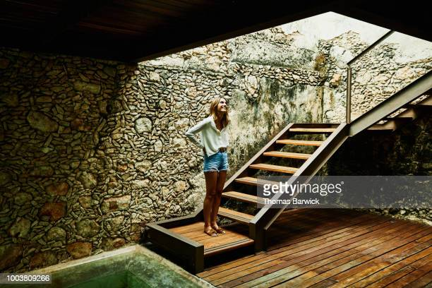 Smiling woman standing at bottom of stairs at luxury resort looking up