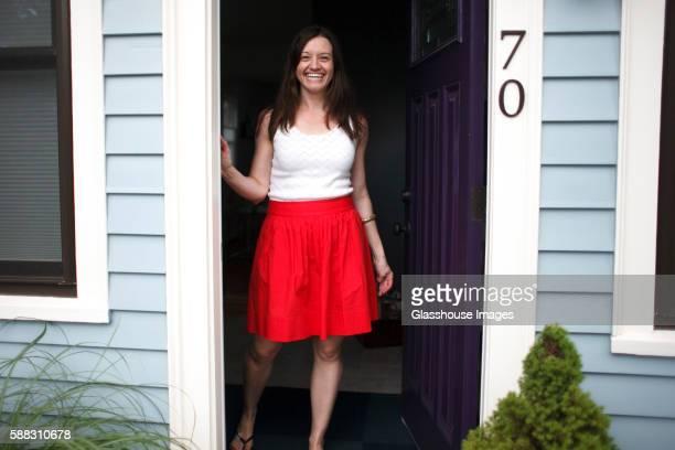 Smiling Woman Standing at Open Front Door