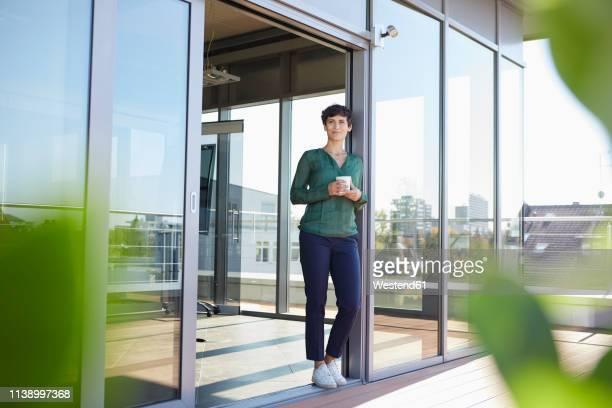 smiling woman standing at the window having a coffee break - pause machen stock-fotos und bilder