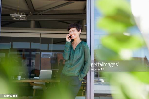 smiling woman standing at the window talking on cell phone - grün stock-fotos und bilder