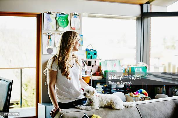 smiling woman standing behind couch petting dog - alleen één mid volwassen vrouw stockfoto's en -beelden