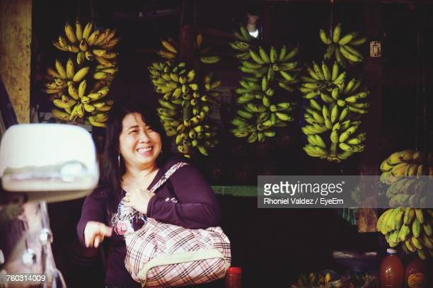 smiling woman standing by bananas for sale at market - greater manila area stock-fotos und bilder
