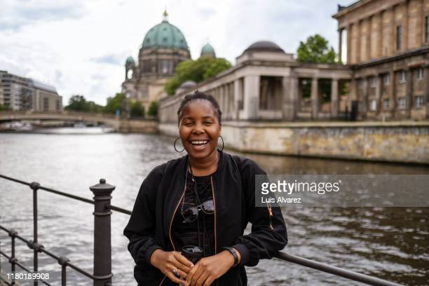 smiling woman standing by spree river in city - travel stock pictures, royalty-free photos & images