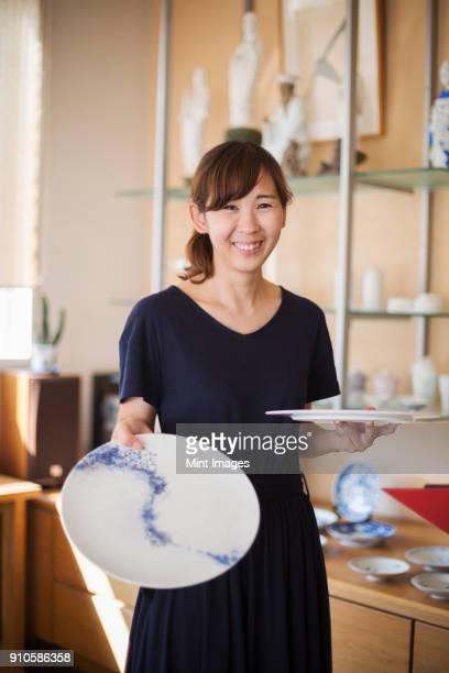 smiling woman standing in a japanese porcelain shop, holding two white plates with blue decoration. - 佐賀県 ストックフォトと画像