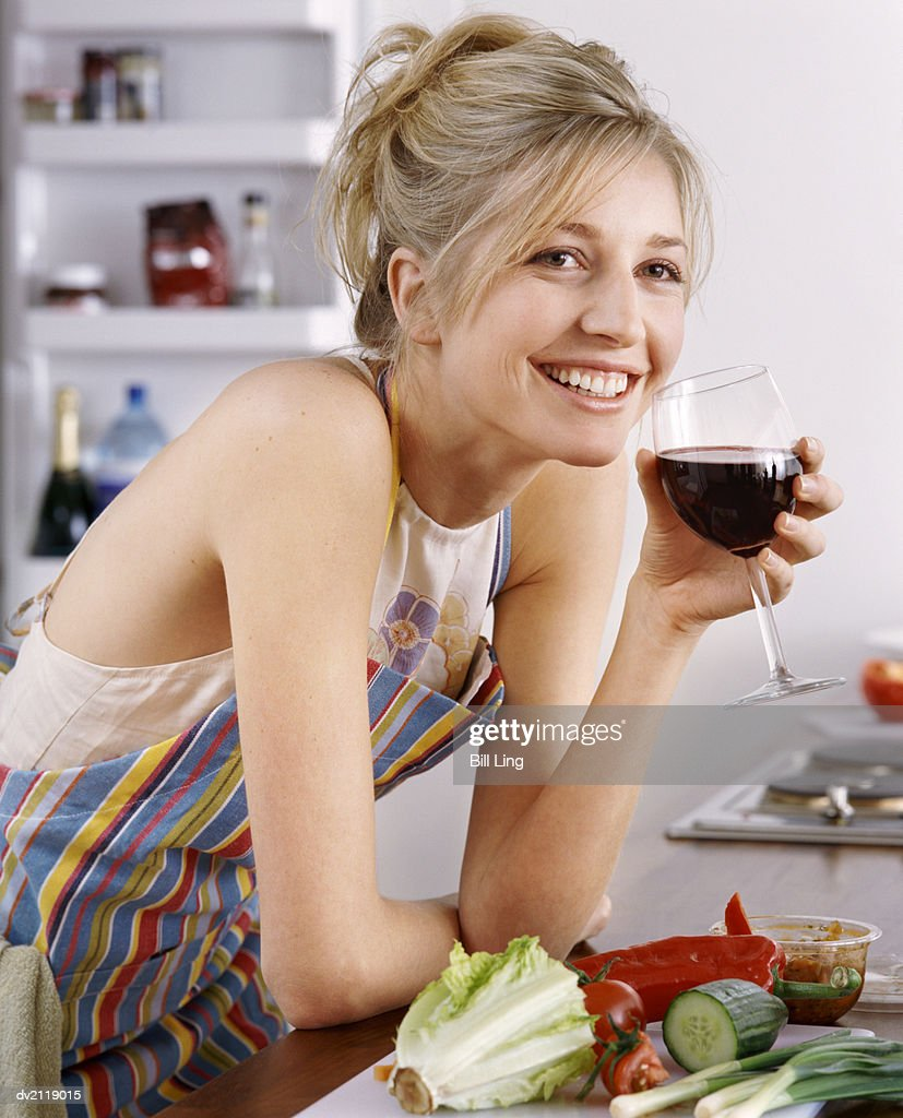 Smiling Woman Standing in a Kitchen Holding a Glass of Red Wine : Stock Photo