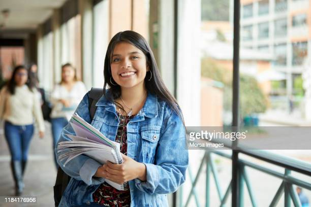 smiling woman standing in corridor at university - college students stock pictures, royalty-free photos & images
