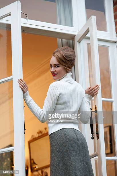 smiling woman standing in doorway - beehive hair stock pictures, royalty-free photos & images