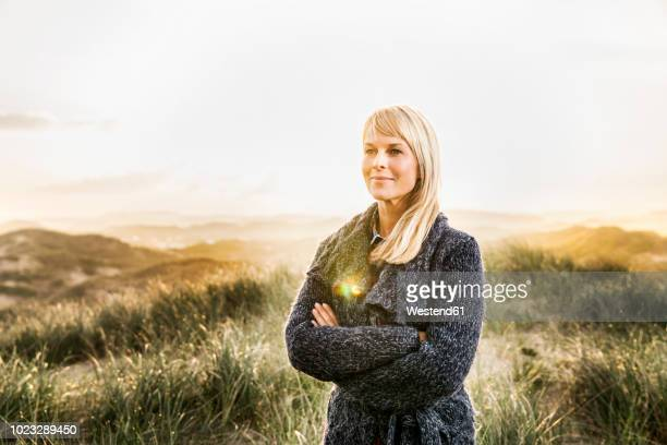 smiling woman standing in dunes - back lit stock pictures, royalty-free photos & images