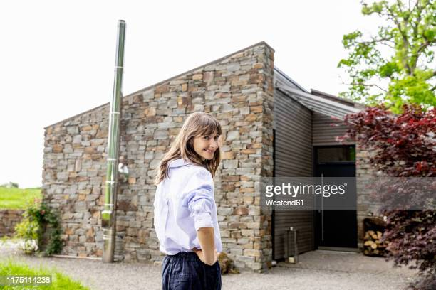 smiling woman standing in front of a house - chemisier blanc photos et images de collection