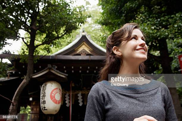 Smiling woman standing in front of building, Japan