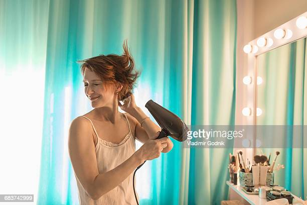smiling woman standing in front of mirror at dressing table - secador de cabelo - fotografias e filmes do acervo