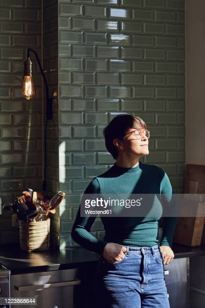 smiling woman standing in kitchen at home with closed eyes - pessoas serenas imagens e fotografias de stock