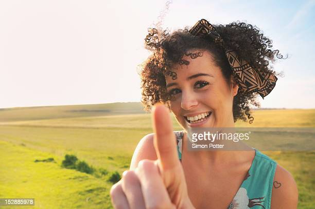 smiling woman standing in meadow - pointing stock photos and pictures