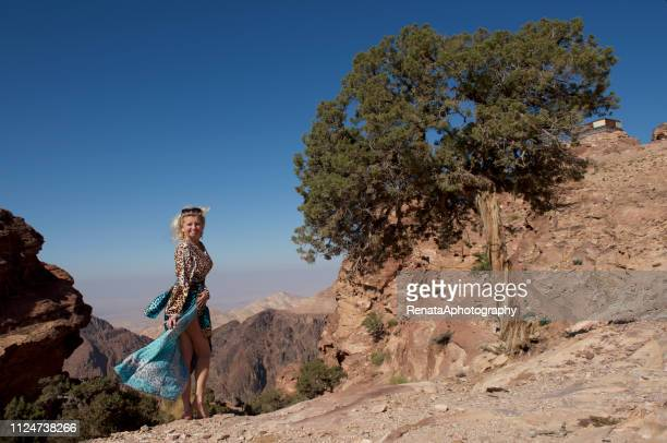 smiling woman standing in mountains, petra, wadi musa, jordan - long dress stock pictures, royalty-free photos & images