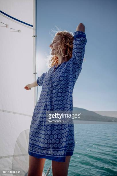 Smiling woman standing on a sailing boat