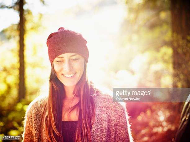 Smiling woman standing on hillside in forest