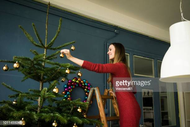 smiling woman standing on ladder decorating christmas tree - pendant light stock pictures, royalty-free photos & images