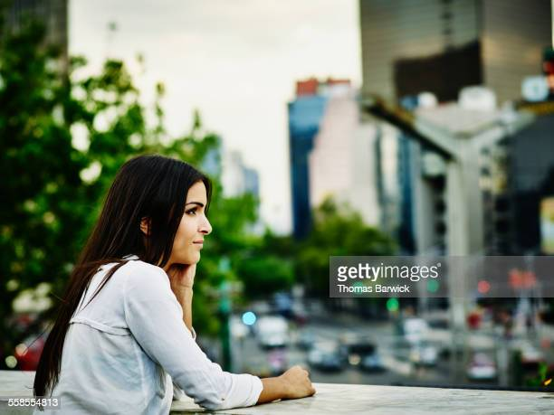 Smiling woman standing on terrace overlooking city