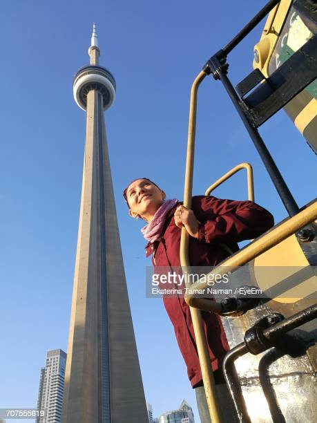 Smiling Woman Standing On Vehicle Against Cn Tower In City