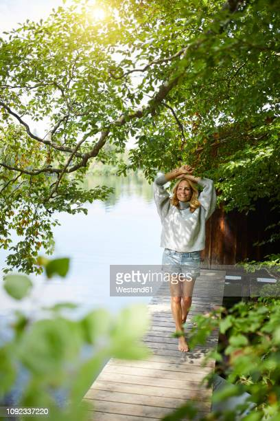 smiling woman standing on wooden jetty at a remote lake - tranquil scene stockfoto's en -beelden