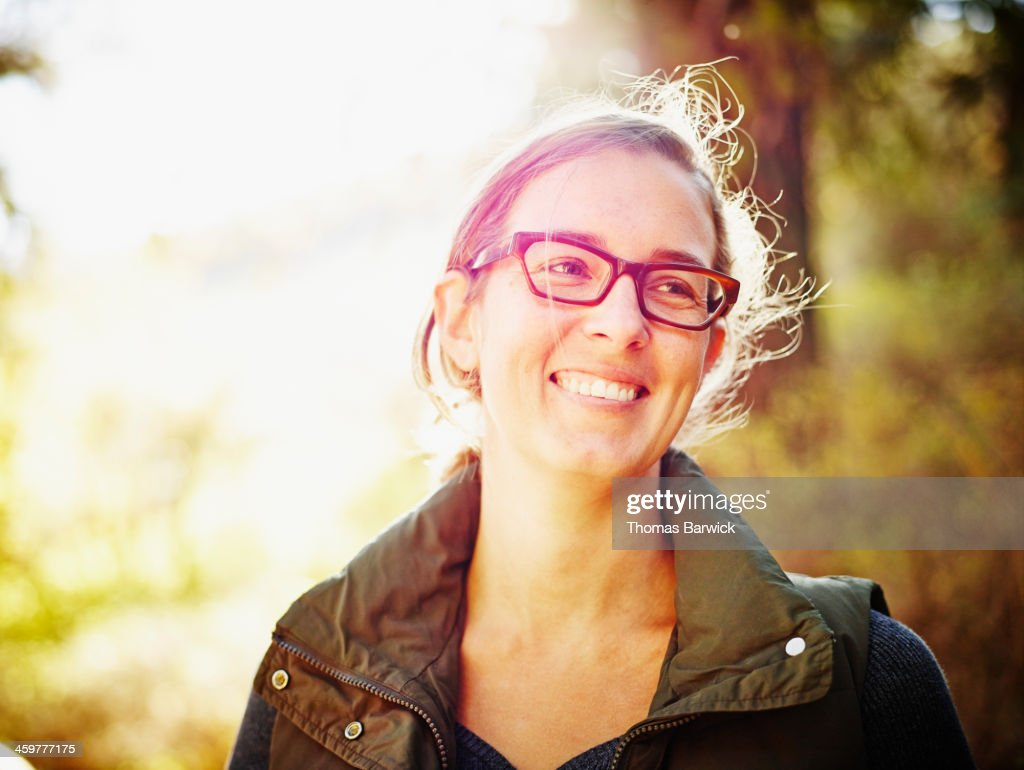 Smiling woman standing outdoors in forest : Stock Photo