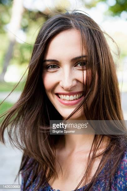smiling woman standing outdoors - cheveux bruns photos et images de collection