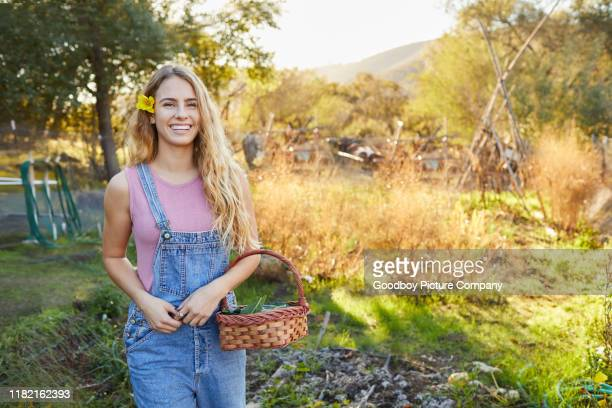 smiling woman standing with a basket in her vegetable garden - green fingers stock pictures, royalty-free photos & images