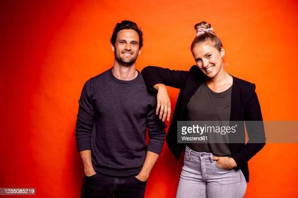 smiling woman standing with hand on man's shoulder against orange background - heteroseksueel koppel stockfoto's en -beelden