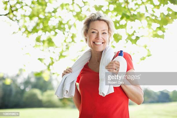 Femme souriante avec une bouteille d'eau et serviette