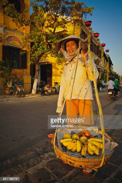 Smiling woman street vendor along the riverfront at sunset in Hoi An, Vietnam. Hoi An is located on the coast of the South China Sea in central...