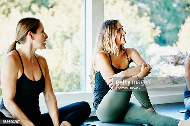 Smiling woman stretching before yoga class